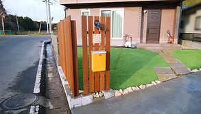 変形敷地は有効活用して2ヵ所の駐車スペースに、アプローチ脇のお庭は人工芝を敷き多目的スペースにしました。木製目隠しフェンスで外からの視線を遮り、人工芝はお客様が購入したものでコストを抑えました。