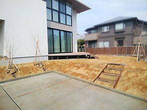 天然芝TM9を庭一面に敷いたおしゃれなエクステリア。建物の外壁に映し出された植栽の陰影が幻想的です。駐車場とお庭の高低差があるために、法面に簡易階段を設置しました。フェンスは、見えるところはアルミフェンスに、見えないところはメッシュフェンスにしてコストダウンしています。サイクルポートや物置も設置し、使いやすいエクステリアになりました。