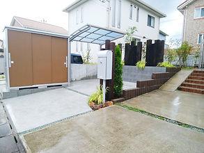 芝生の法面を削って型枠ブロックで土留めをし、駐輪場と物置スペースを作りました。中庭には、ウッドデッキやサンルーフを設置して、植栽を配置した憩いのスペースを作成。プライバシー対策として、スクリーンや枕木を設置し目隠し対策も万全です。