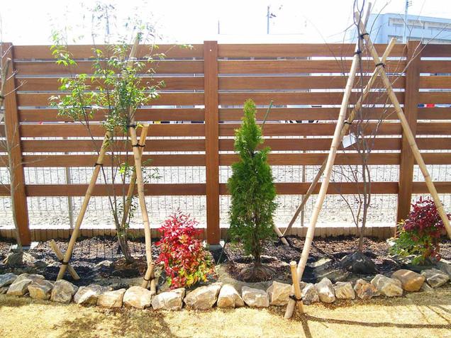 木製フェンスとミカモ石の花壇