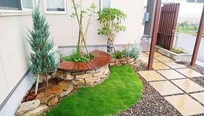 サークルベンチ、ガーデンゲートと石貼り花壇で高級感を演出したセミクローズド玄関。カーポート、サイクルポートから玄関まで動線・目線に配慮したデザインです。お庭にはレッドシダーのウッドデッキを設置。植栽もバランスよく配置しています。