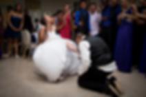 Bride with kneeling husband in garter toss ceremony