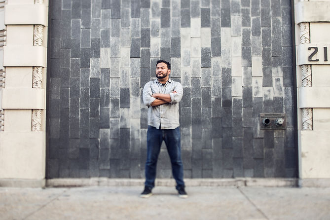 New Orleans Based Photographer Trevor Mark poses in front of a gray brick wall