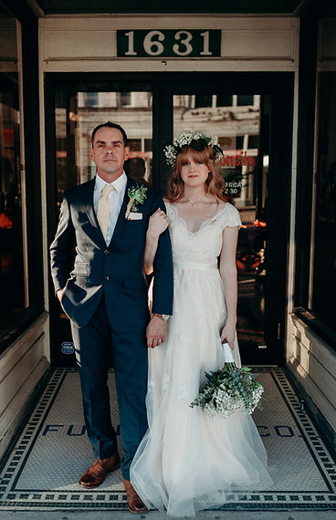 A couple in Tuxedo and Wedding Gown hold each other close as they pose for a photo in front of local store front.