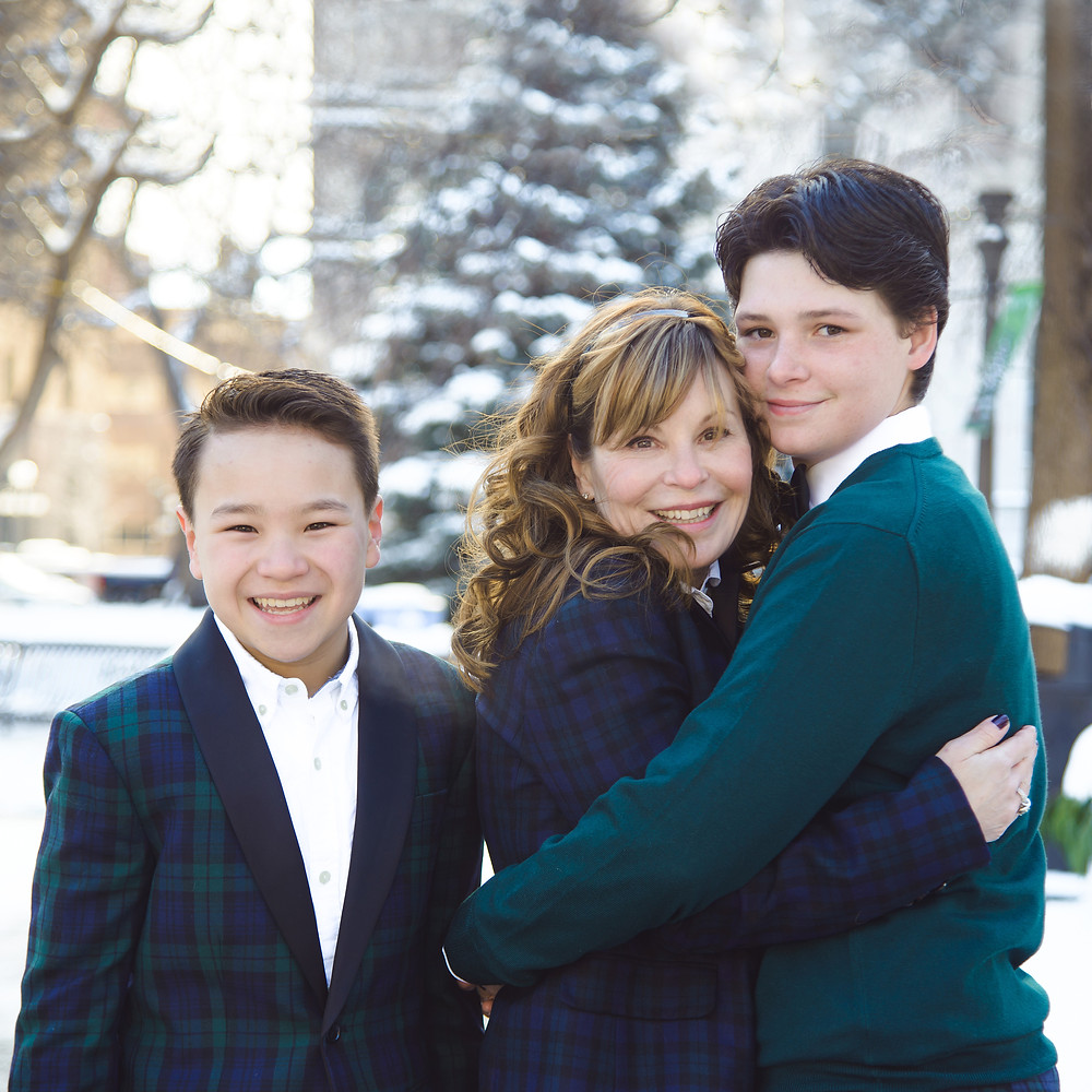 Outdoor portrait of a family of 3. young boy in a plaid blazer, and two women hugging looking at the camera.