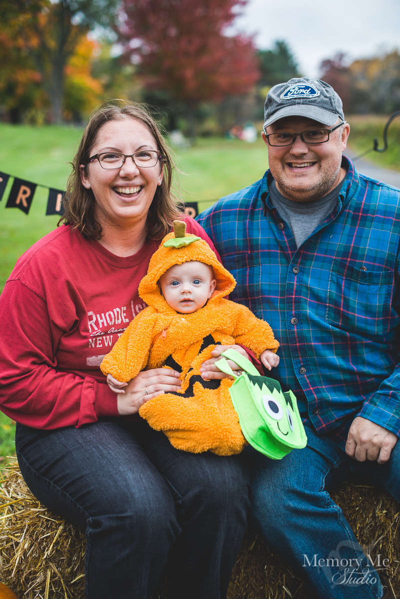 Family photo of three, including a baby dresses as a pumpkin. Mom dad and baby are looking at the photographer.  Portrait captured by Madelin Zaycheck, St. Paul Family Photographer