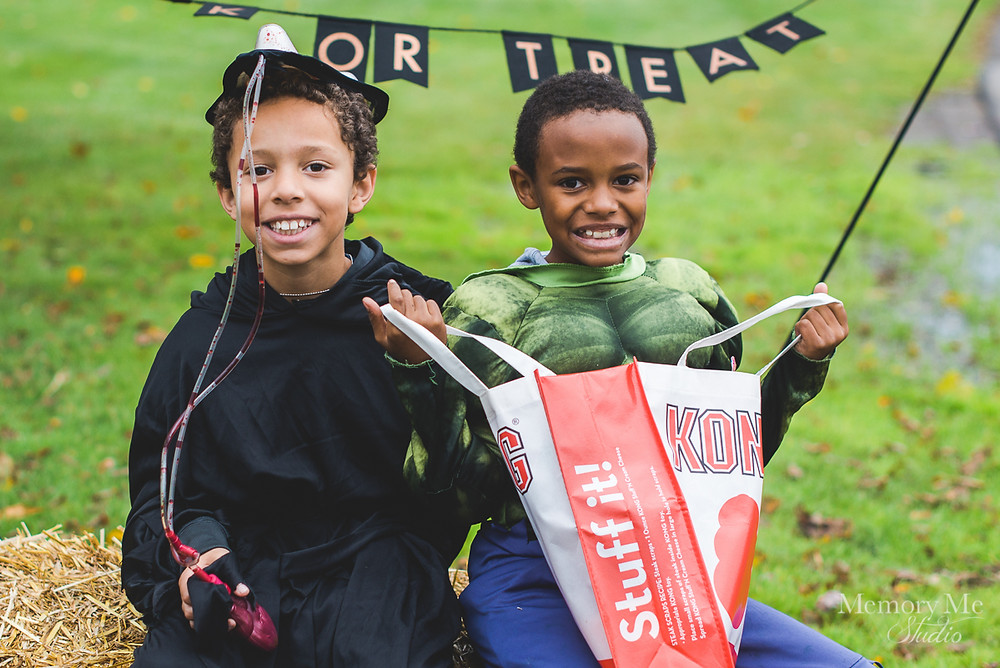 two young black boys wearing halloween costumes smiling at the camera at a photo station in north st. paul.  Portrait captured by Madelin Zaycheck, St. Paul Family Photographer
