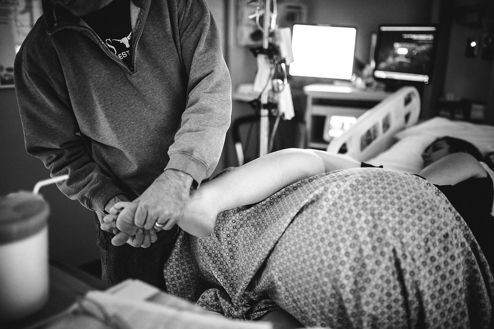 Dad rubbing moms feet during labor at Methodist Hospital in Minnesota | By Madelin Zaycheck St Paul Birth Photographer
