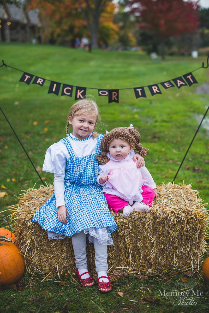 Dorthy and a cabbage patch doll. two young girls in costumes in North Saint Paul at at trick or treat event.  Portrait captured by Madelin Zaycheck, St. Paul Family Photographer