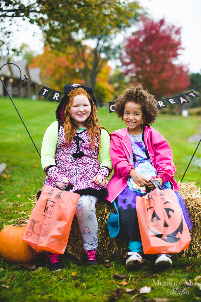 Two young girls smiling at the camera with trick or treat bags at a photo station in north saint paul.  Portrait captured by Madelin Zaycheck, St. Paul Family Photographer