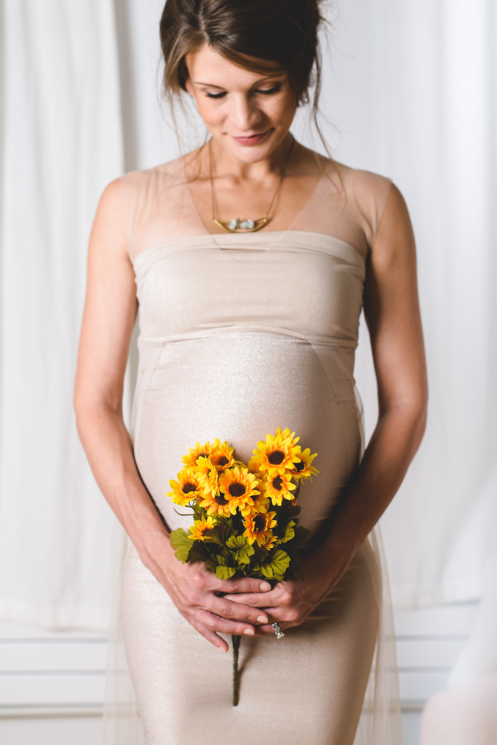 pregnant mother with bouquet of flowers in st paul portrait studio.