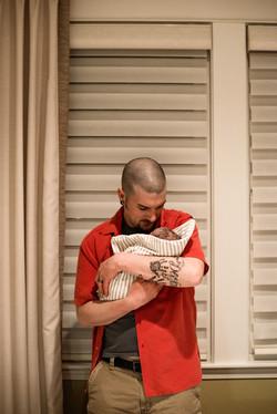 dad holding swaddled newborn
