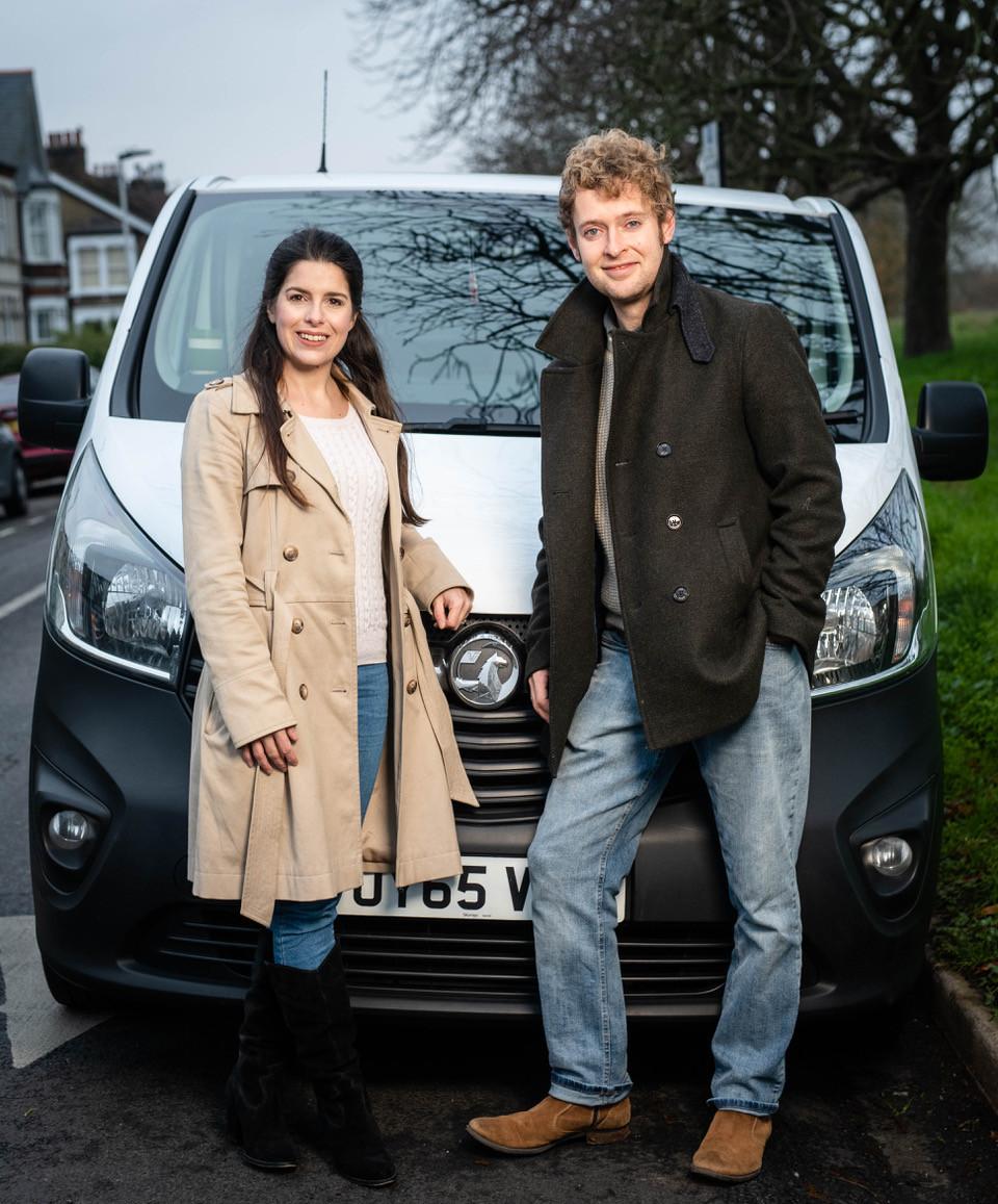 Couple travel bloggers standing in front of a Vauxhall Vivaro van.