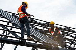 The Roofer technicians work on the roof structure of the building at the construction site