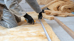 Cropped view of professional workman in protective workwear using knife and holding measur