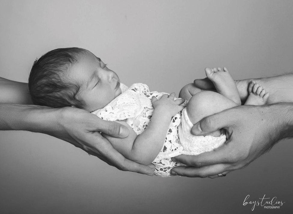 Baby in den Händen seiner Eltern