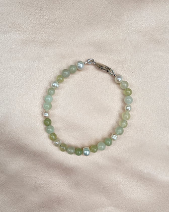 Bracelet made from light green jade and aventurine round beads and white pearls, overhead view.