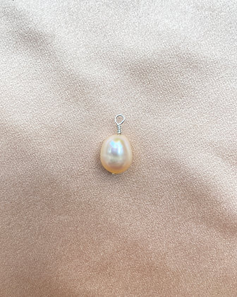 Pink baroque pearl with silver wire loop, overhead view.