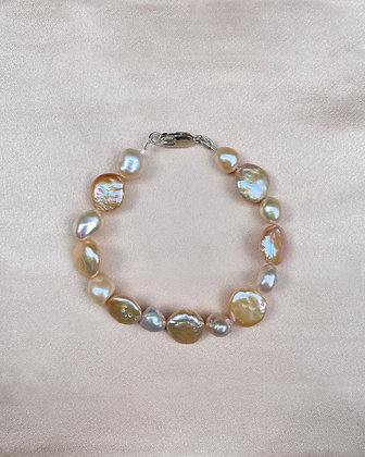 White, cream and peach coin and baroque pearl bracelet, finished with a sterling silver clasp, overhead view.