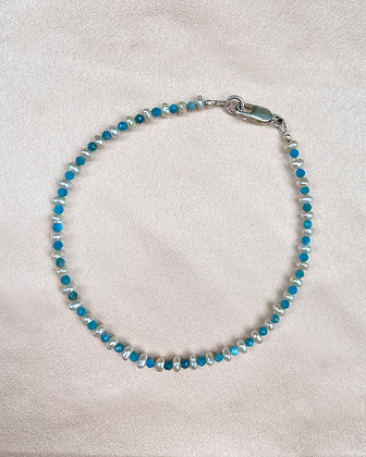Anklet made from alternating blue apatite seed beads and white seed pearls, overhead view.