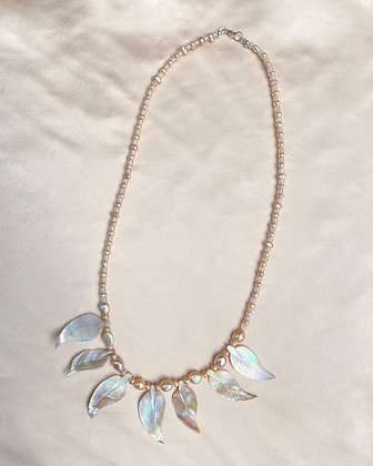 Long pink pearl necklace, featuring seven iridescent mother of pearl feather pendants, overhead view.