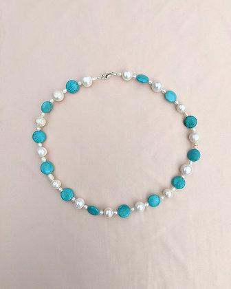 A handmade necklace made from pearls, turquoise coin beads and irregular seed pearls.