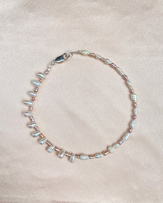 Anklet made from alternating pink seed pearls with white rice pearls on the left side and white seed pearls on the right side