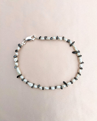 A handmade anklet made from recycled hematite shards and various small pearls.