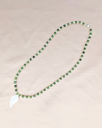 A necklace made from a mother of pearl carved feather, jade andmother of pearl beads. Lying flat on pink fabric.
