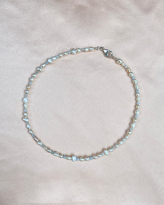 Choker made from seed pearls and aquamarine gemstones, overhead view.