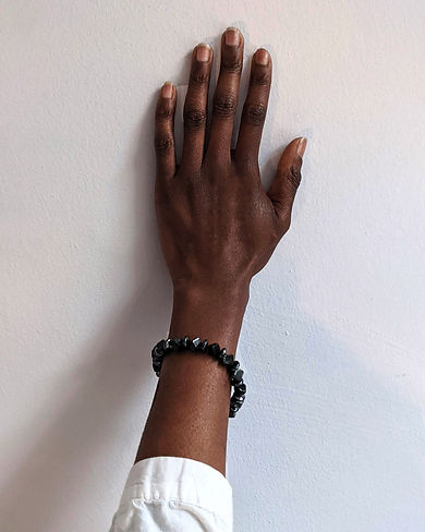 A hand models a black onyx and hematite stretch bracelet. Click this link to shop our 'Black is black' bracelet.