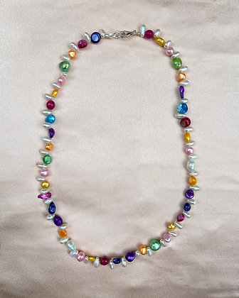 Alternating white rice pearls with brightly dyed pearls in pink, green, yellow, purple, blue and orange. Overhead view.