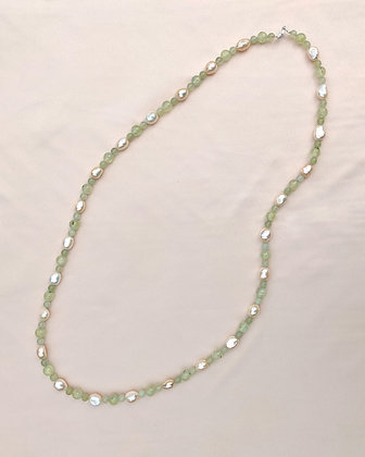 A handmade necklace made from recycled green Aventurine, prehnite,and baroque pearls lying flat on pink fabric.