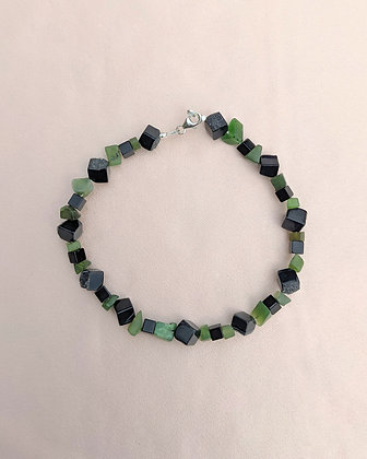 An anklet or bracelet made from Jade Shards, black onyx cubes and black druzy onyx cubes lying on pink fabric