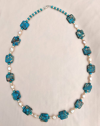 A necklace made from blue Apatite squaresand 'turquoise' button beads, button pearls, and drop pearls lying on pink fabric.