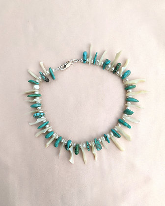 A handmade anklet made from recycled turquoise nuggets, button pearls, and mother of pearl shards lying on pink fabric.