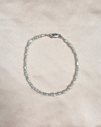 Anklet made from alternating aquamarine seed beads and white seed pearls, overhead view.