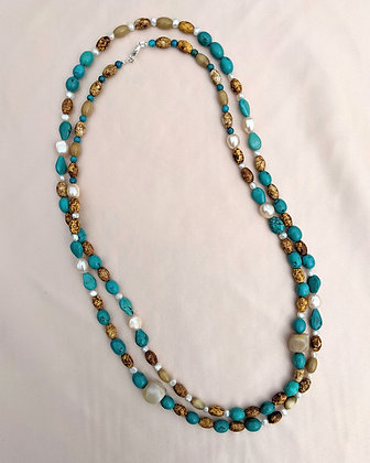 A long necklace of pearls, man madebeads, chrysoberylcat's eye,turquoise and carnelian semi precious stones.