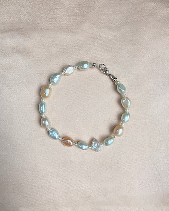 Bracelet/anklet made from alternating tiny seed pearls with white, pale green and peach baroque pearls, overhead view.