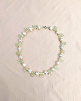 A recycled jade and pearl necklace lying on pink fabric.