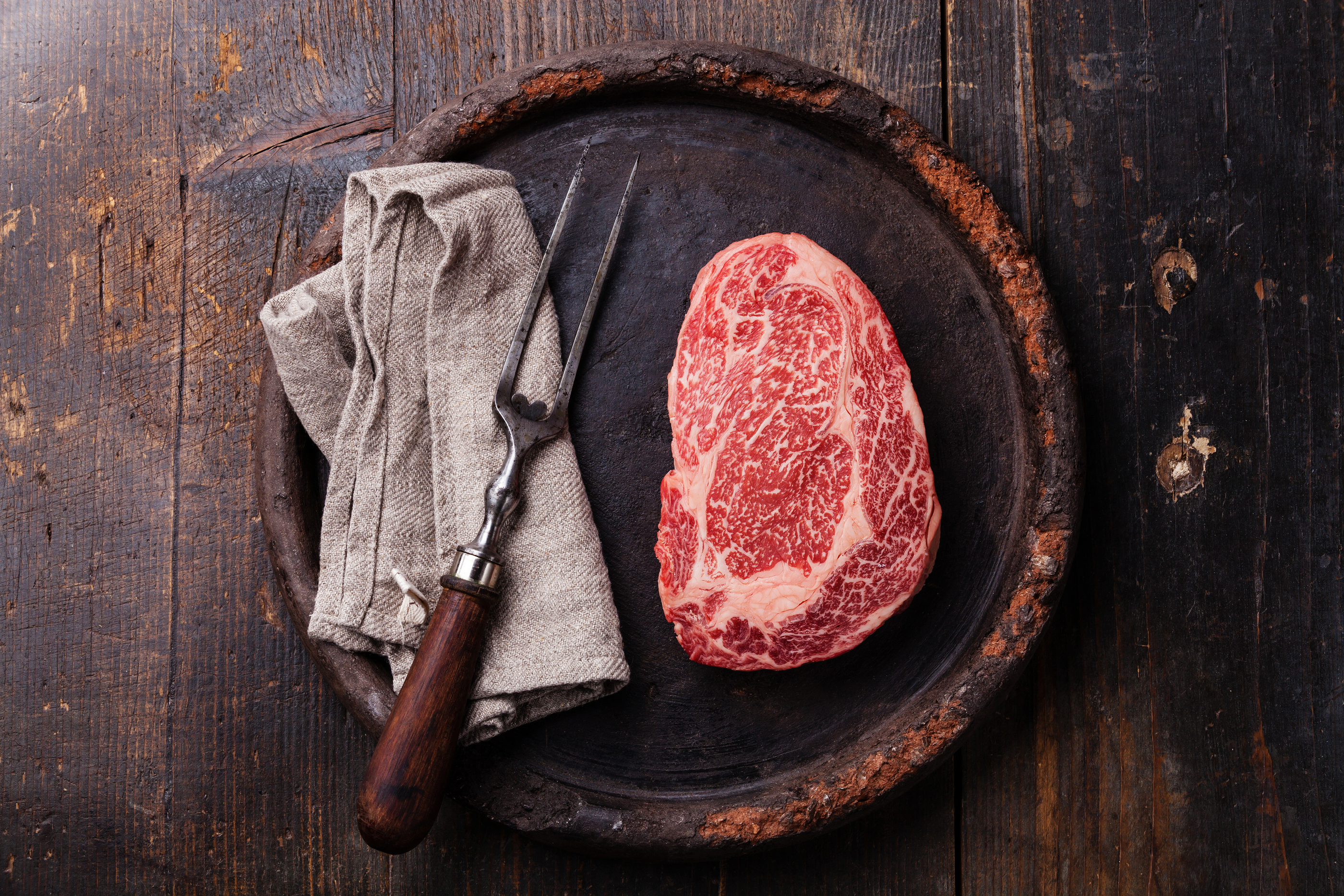 Raw Fresh Marbled Meat Black Angus Steak Ribeye And Meat Fork On Dark Background