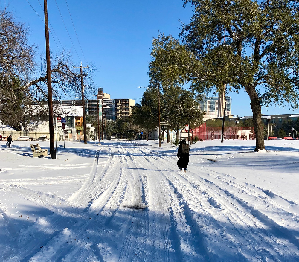 Labor Street covered in snow with some tire tracks and Jane Gennarelli walking toward the north.