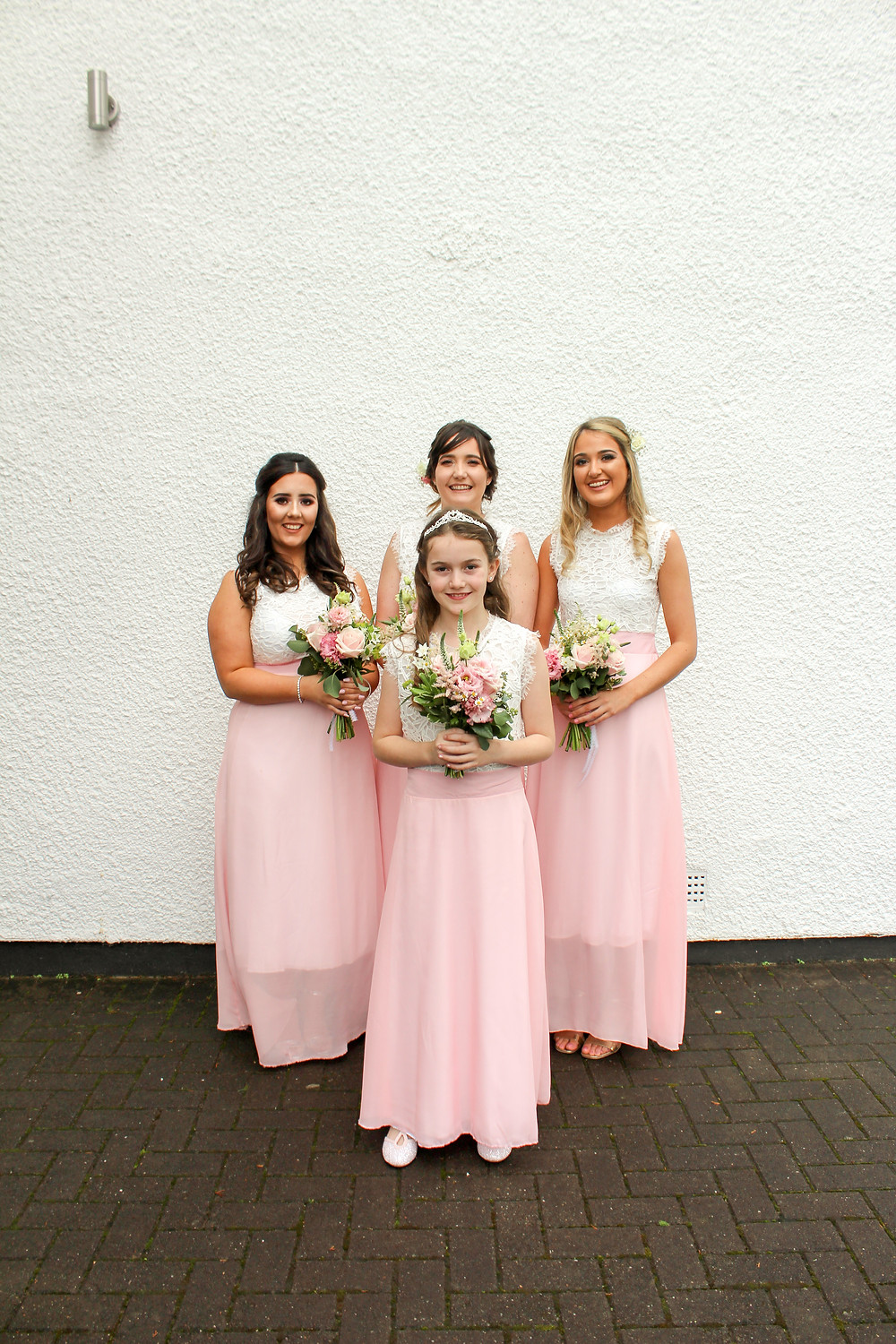 Four girls stand against a white wall. all four are wearing matching dresses with a white lace top and pink long skirts, they are holding pink flowers