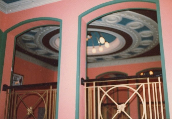 Interior of building showing pink and green patterns and ornate ceiling rose