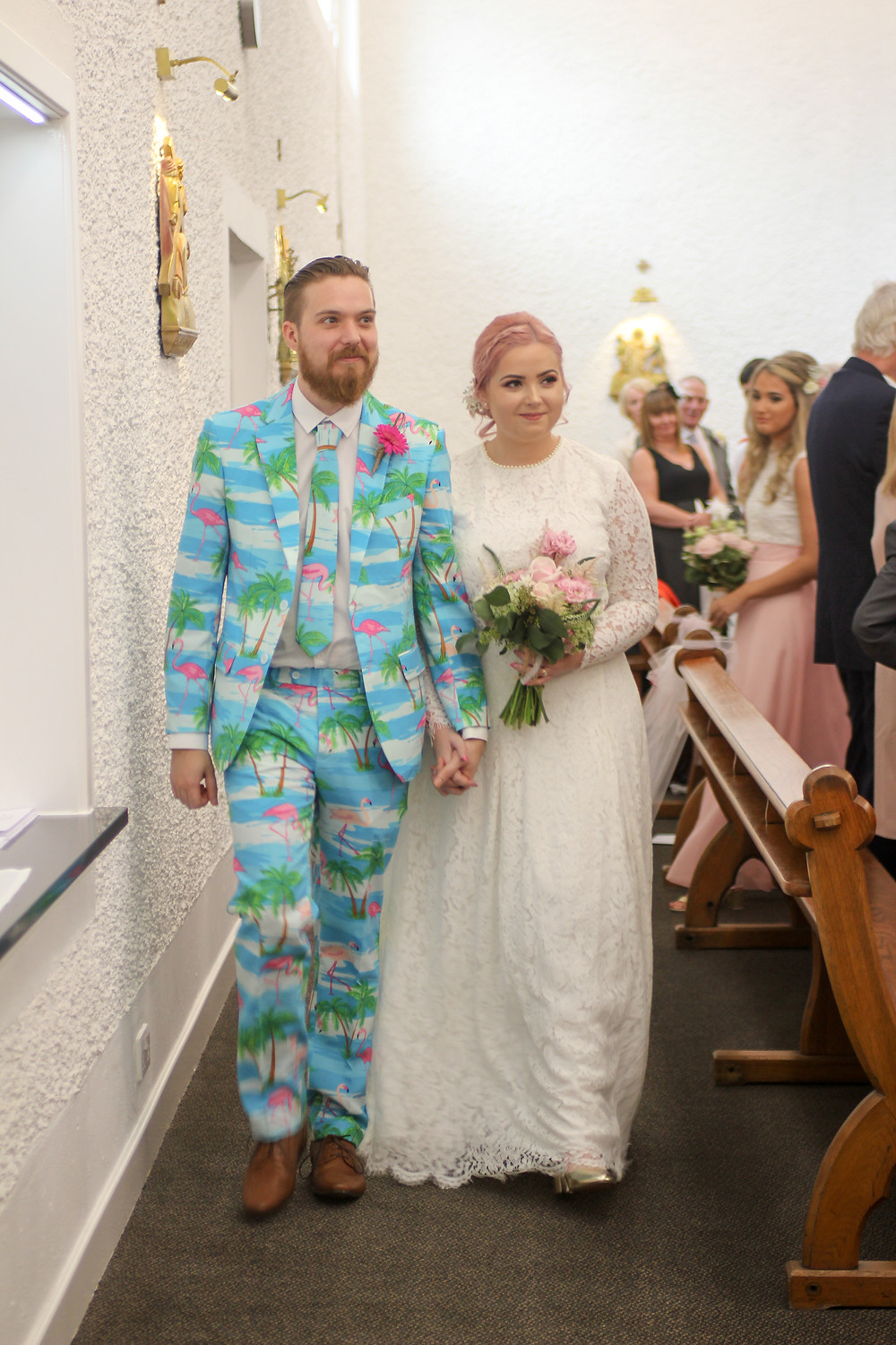 Bride and groom are at the back of a church, the groom is wearing a white and turquoise suit with pink flamingos, the bride is wearing a white lace dress with long hair and has pink hair tied back
