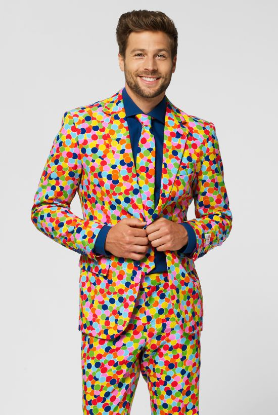 Model wears confetti print suit with multiocoloured dots and a navy shirt