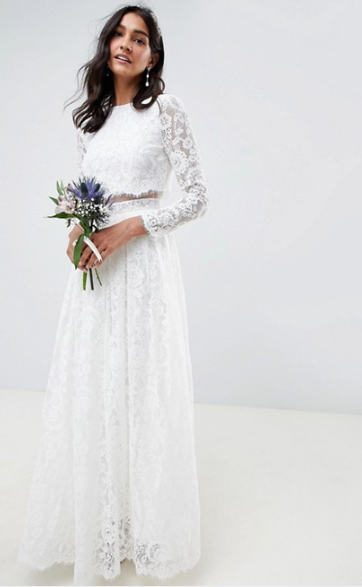 Model with long dark hair wears a long sleeved white lace wedding dress