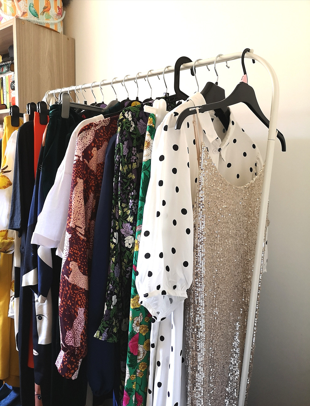 Clothes hang on a white metal rail against a white wall and wooden bookcase. The clothes are all different patterns, there is a gold sequinned dress, a black and white polka dot dress and floral prints.