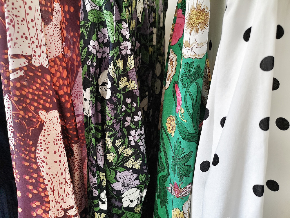 A close up of fabrics including a burgandy shirt with big cats, a dark green fabric with green flowers, a bright green floral and a black and white polka dot