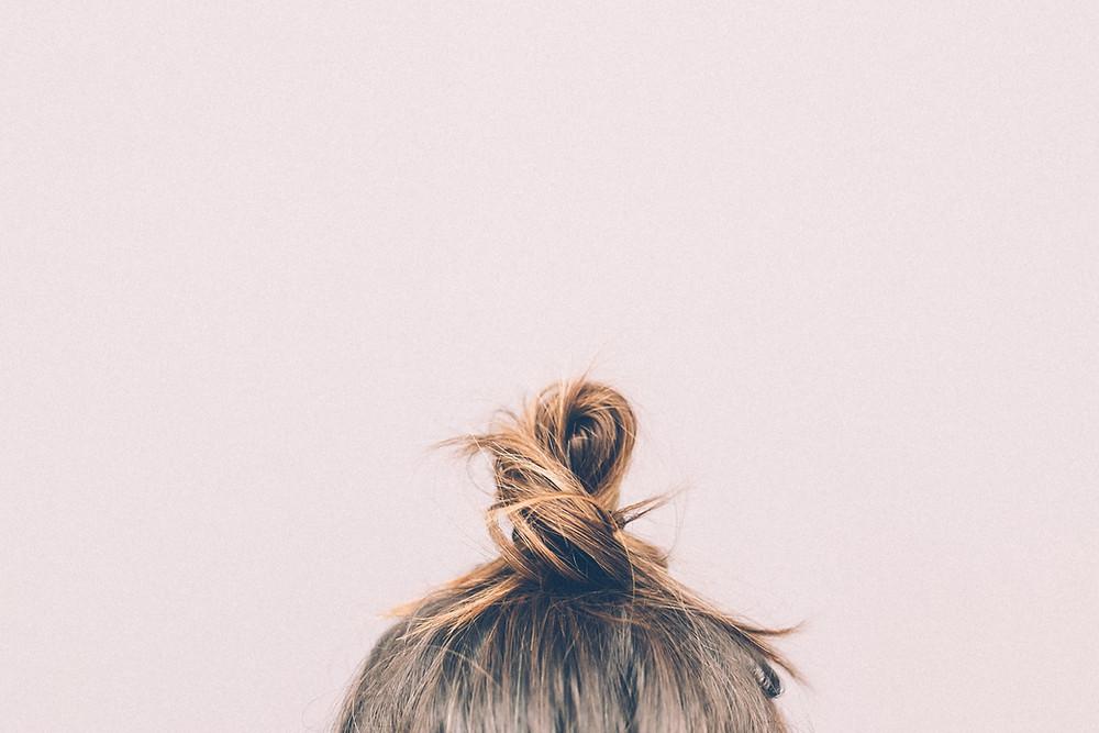 Girls hair tied in bun against pink background